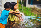 children-playing-with-water-in-garden